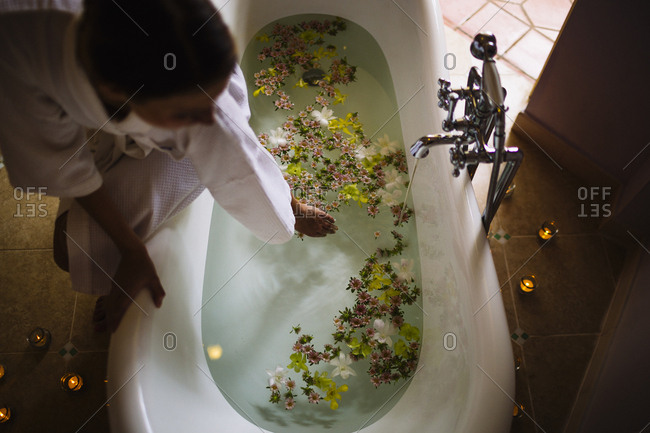 Woman filling a bathtub with water and flowers at a luxury resort