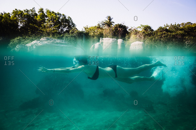 Young woman swimming underwater off an island in southern Vietnam
