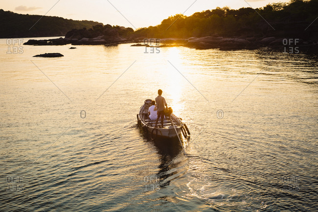 Young man steering a boat toward an island at sunrise in southern Vietnam
