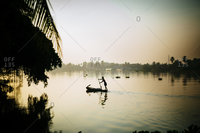 Fisherman paddling a boat on the Saigon River in the early morning