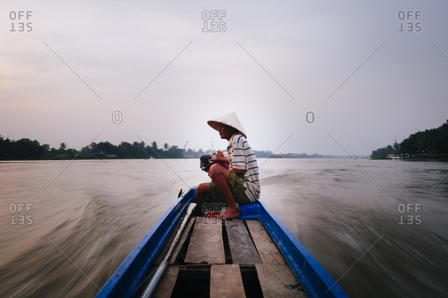 Ho Chi Minh City, Vietnam - December 16, 2015: Main sitting on the end of a small boat moving down the Saigon River