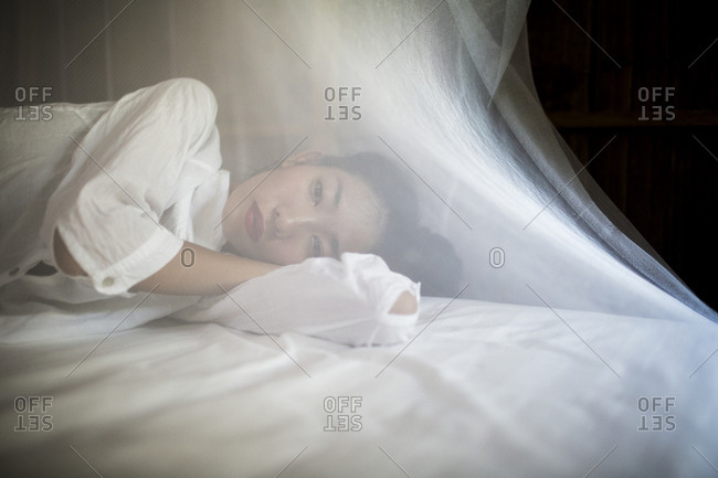 Young Asian woman lying on a white bed with netting