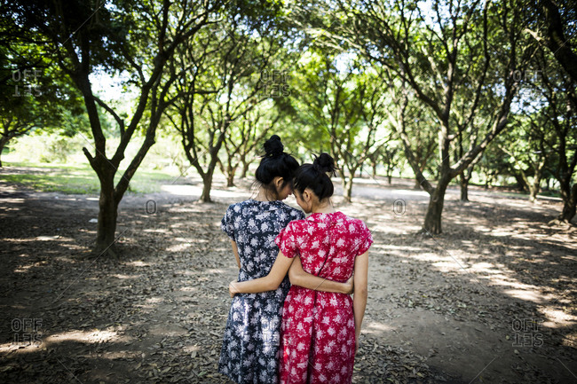 Two Vietnamese sisters in summer dresses walking and embracing in a garden