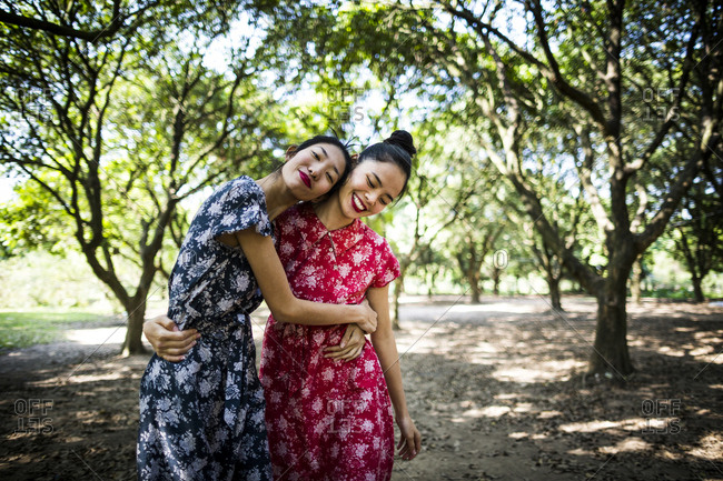 Two Vietnamese sisters in summer dresses embracing in a garden