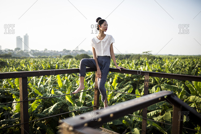 Young Vietnamese woman on a bridge with rice fields and skyscrapers behind her