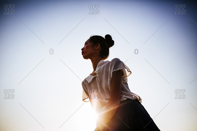 Stylish young Vietnamese woman with the sun shining behind her