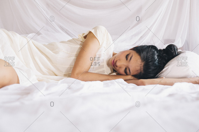 Vietnamese woman in a white slip lying in bed