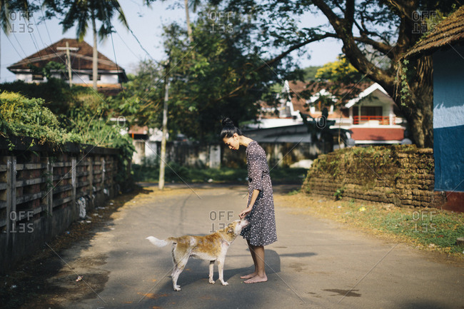 Barefoot woman petting a stray dog on a small street in Kochi, India