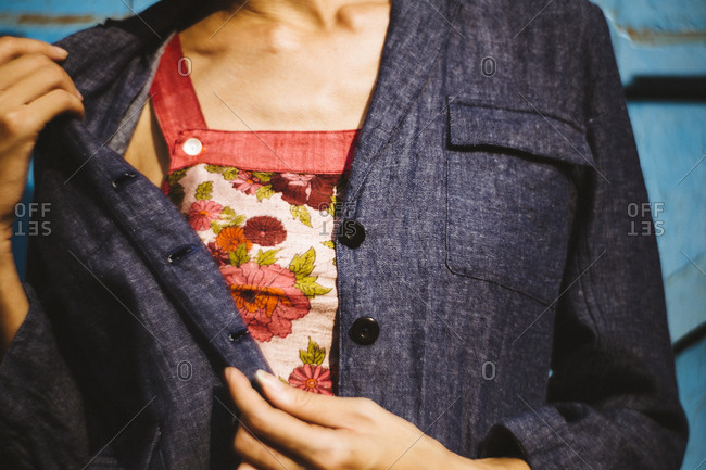 Woman pulling back a denim jacket to reveal a colorful floral shirt