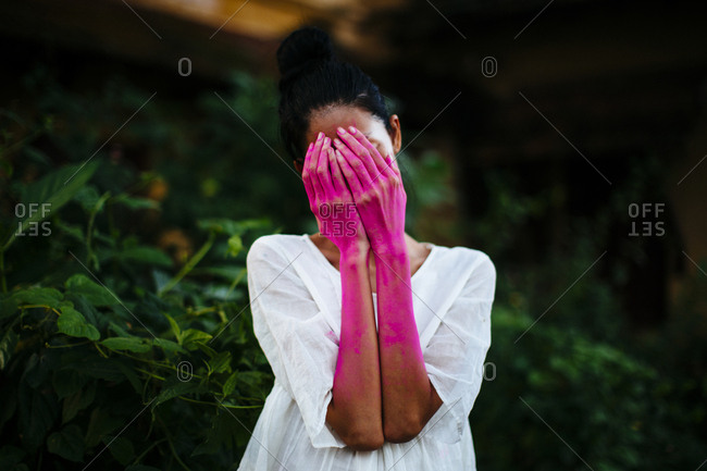 Woman with bright pink dye on her hands hiding her face