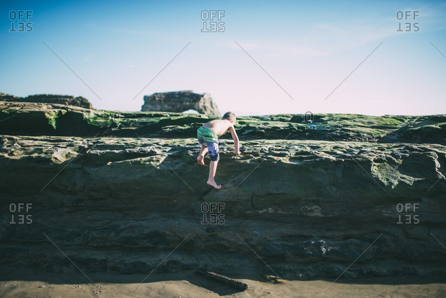 Little boy climbing on rocks at a beach