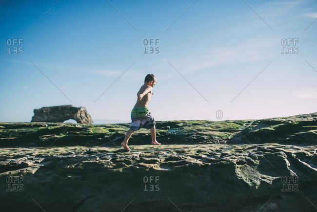 Boy rocking along a rock wall at a beach