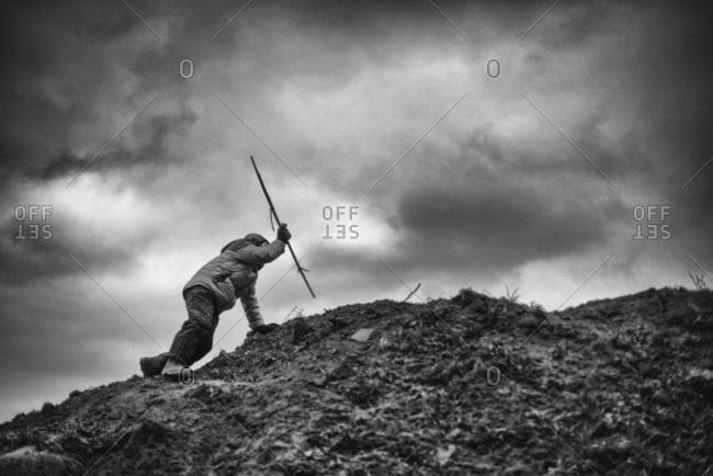 Kid putting stick into dirt at the top of a hill in black and white