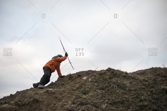 Kid putting stick into dirt at the top of a hill