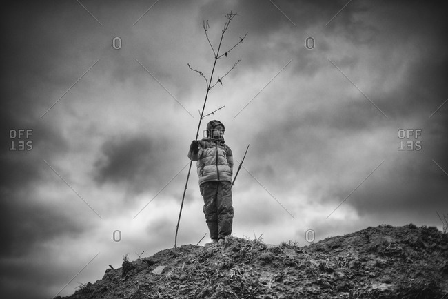 Child standing with tree branch at the top of a hill in black and white