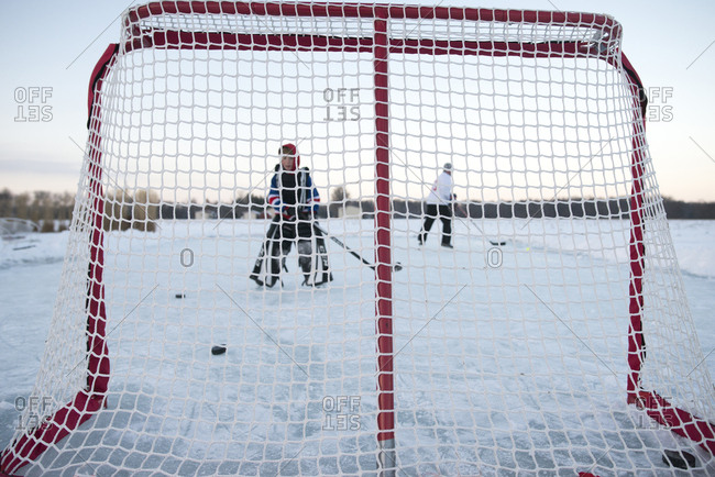 Child shooting puck into hockey goal