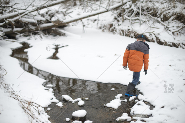 Young boy walking in a snowy river