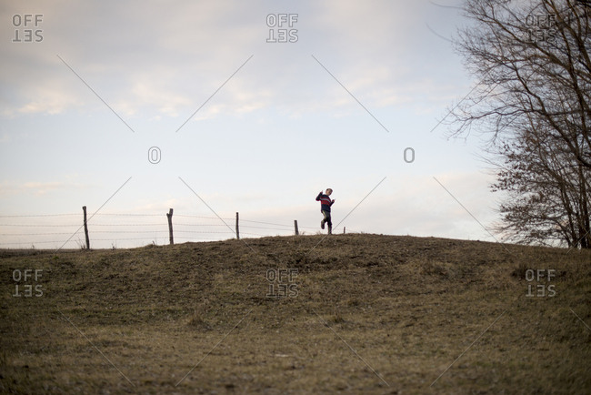 Boy dancing on top of a hill
