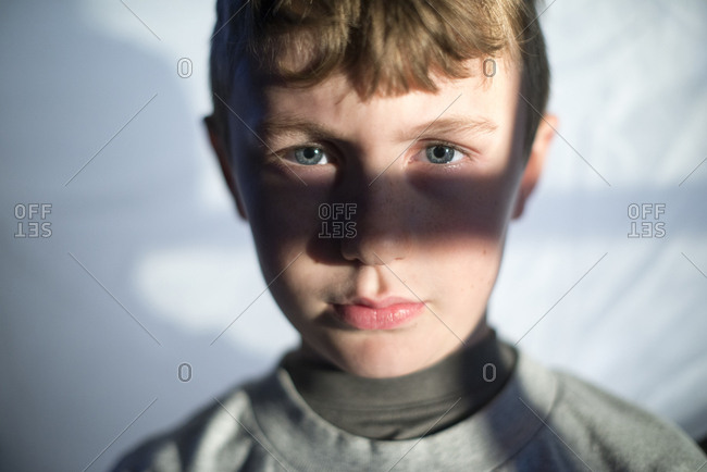 Portrait of a blond boy with blue eyes standing in window light
