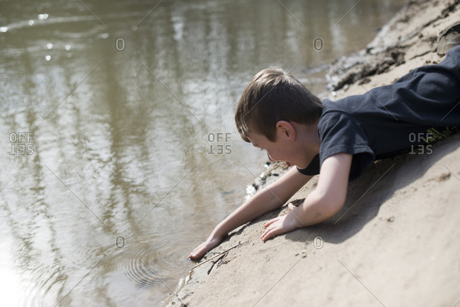 Young boy lying on a riverbank reaching into the water
