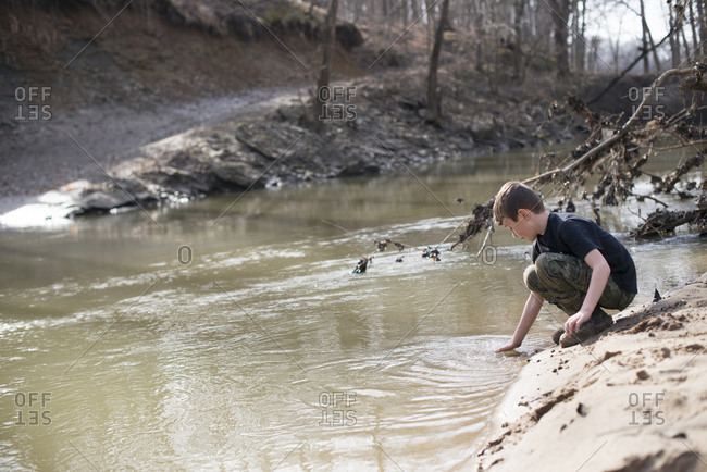 Young boy on a riverbank reaching into the water
