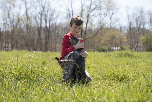 Boy petting kitty in a field