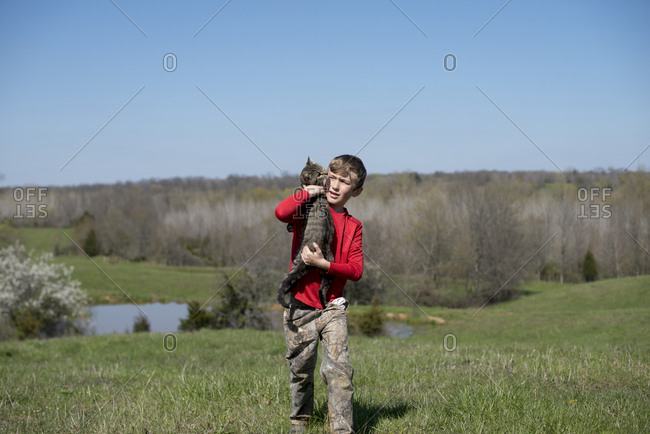 Boy carrying kitty in a field