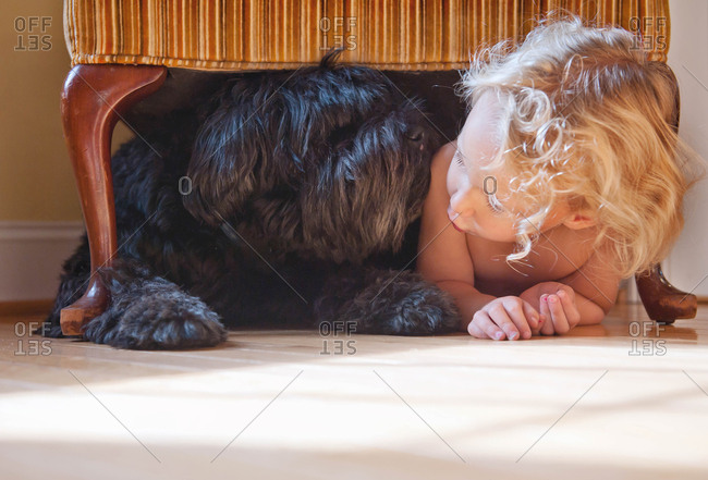 Little girl under a chair with her dog