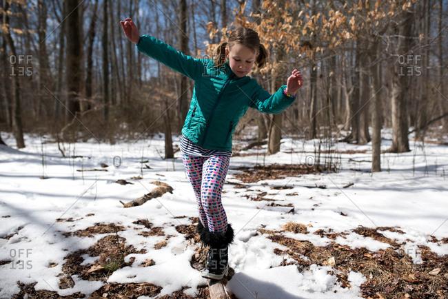 Little girl walking on a log in winter