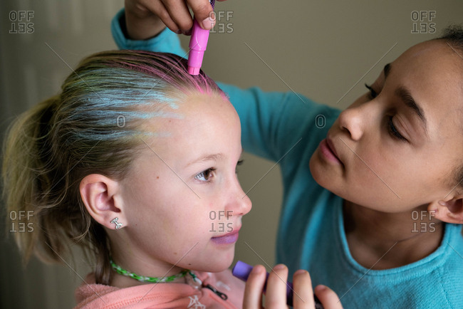 Little girl coloring blonde girls hair with hair chalk