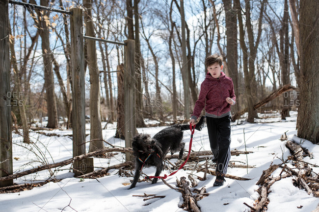 Boy running in snowy forest with a shaggy dog