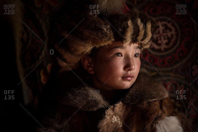 Altai Mountains, Mongolia - July 18, 2016: Young Kazakh girl in a traditional winter coat and hat