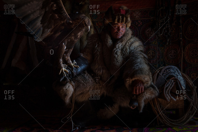 Altai Mountains, Mongolia - July 18, 2016: Kazakh hunter with a golden eagle and traditional winter coat