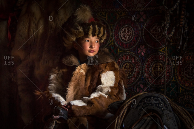 Altai Mountains, Mongolia - July 18, 2016: Young Kazakh girl in a traditional winter coat and hat hugging her knees