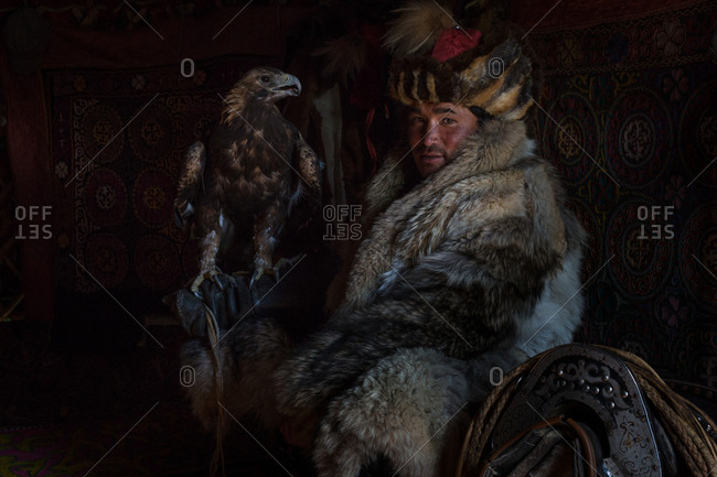 Altai Mountains, Mongolia - July 18, 2016: Kazakh eagle hunter in traditional winter coat and hat