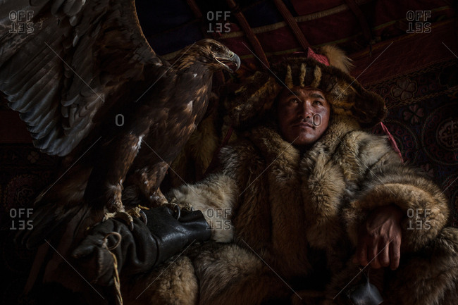 Altai Mountains, Mongolia - July 18, 2016: Kazakh hunter in traditional clothing with a golden eagle spreading its wings