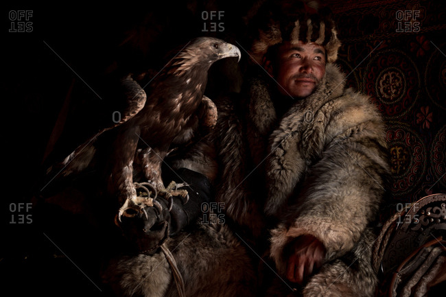 Altai Mountains, Mongolia - July 18, 2016: Kazakh hunter with a golden eagle in traditional winter clothing