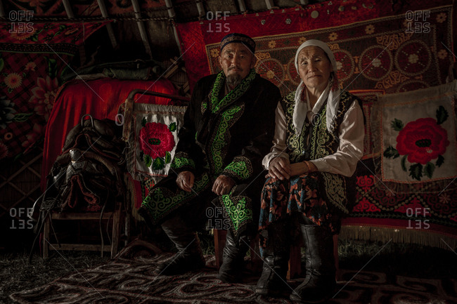 Altai Mountains, Mongolia - July 16, 2016: Senior Kazakh couple in traditional clothing in a tent lined with tapestries