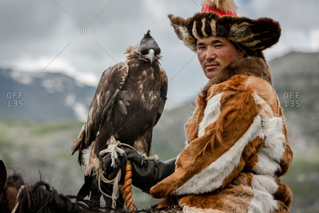 Altai Mountains, Mongolia - July 20, 2016: Kazakh hunter sitting horseback with a golden eagle