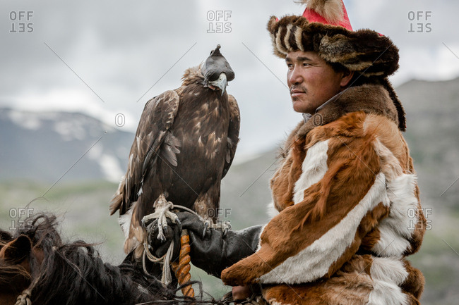 Altai Mountains, Mongolia - July 20, 2016: Kazakh hunter in traditional clothing sitting horseback with a golden eagle