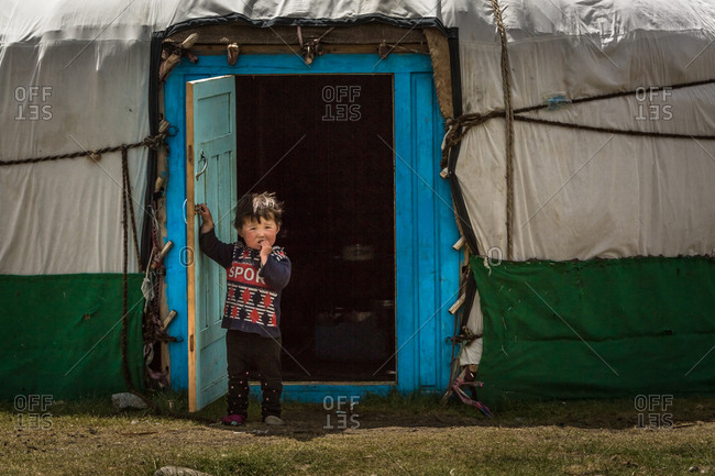 Altai Mountains, Mongolia - July 20, 2016: Kazakh boy standing at the open door of a traditional shelter