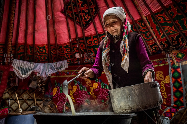 Altai Mountains, Mongolia - July 20, 2016: Senior Kazakh woman stirring milk with a ladle in a traditional ger