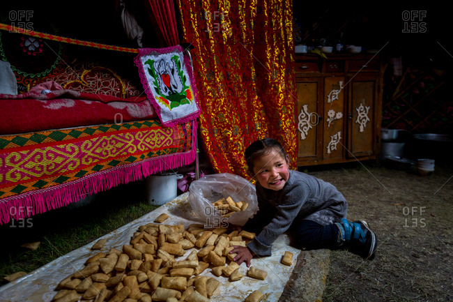 Altai Mountains, Mongolia - July 20, 2016: Kazakh girl putting food into a plastic bag in a traditional ger