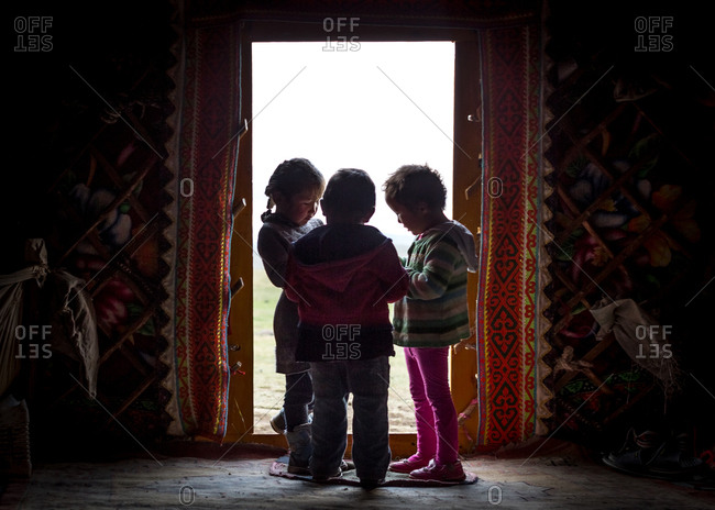 Altai Mountains, Mongolia - July 20, 2016: Three Kazakh children standing together in the doorway of a traditional shelter