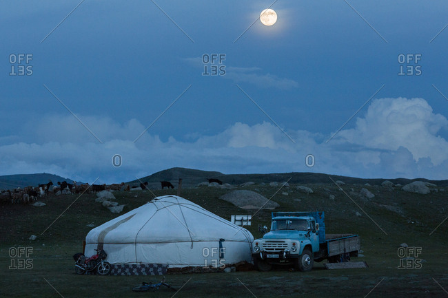 Altai Mountains, Mongolia - July 20, 2016: Moonrise over a ger and old truck parked in a plain