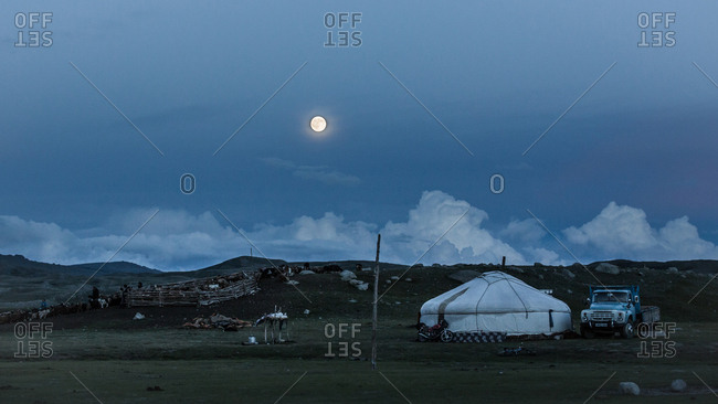 Altai Mountains, Mongolia - July 20, 2016: Moonrise over a ger and livestock in a plain