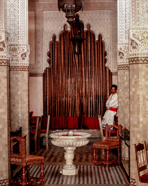 Marrakech, Morocco - May 10, 2010: Man leaning against a tiled column in an empty restaurant