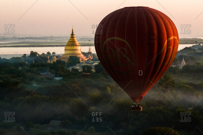 Bagan, Myanmar - December 5, 2012: Hot air balloon flying in the mist near a golden Buddhist temple in Old Bagan