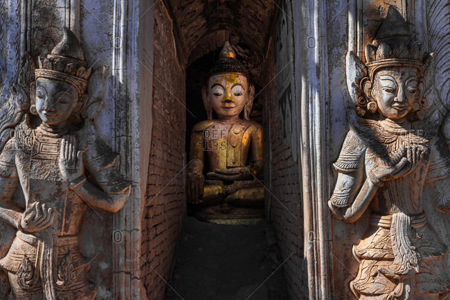 Golden Buddha statue in a decaying temple at Inle Lake, Myanmar