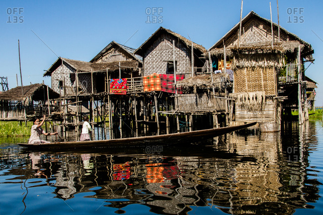 Inle Lake, Myanmar - December 10, 2012: Woman and her daughter paddling a canoe past houses on stilts